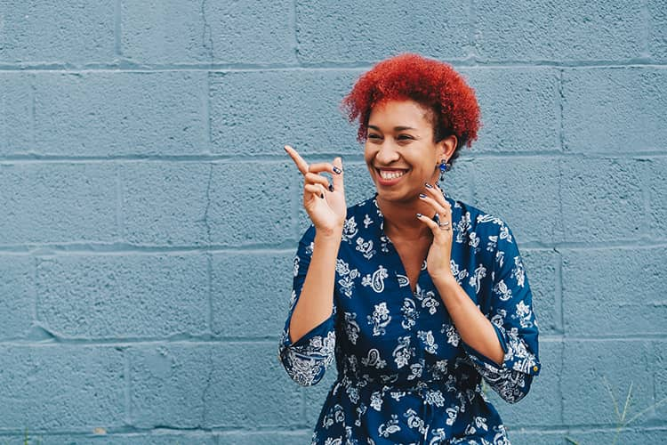 black woman red hair smiling blue wall