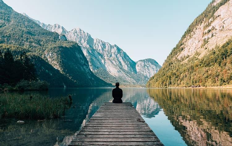 man sitting on grey dock lake