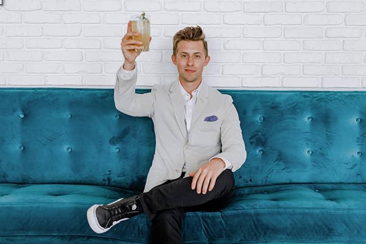man grey blazer raises drink blue couch